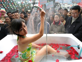 Voyeurs watch a woman bathing at art show